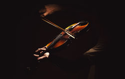 Act of a Violin Player. Adult man is playing a violin, in dark ambiance, showing emotions and expressions Royalty Free Stock Images