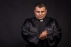 Acteur dans l'image du prêtre sur un fond foncé photos libres de droits