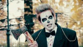 Acteur masculin dans le costume de style de zombi montrant le rire mauvais, tenant la hache ensanglantée dans des mains clips vidéos