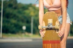 Acticity y concepto de las vacaciones de verano - cercano para arriba de la mano femenina que sostiene el monopatín Foto de archivo