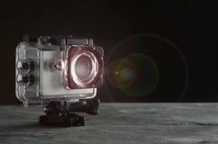 Actiecamera met lensgloed op zwarte achtergrond stock foto