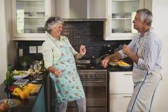 Actief hoger paar die in keuken dansen stock afbeeldingen