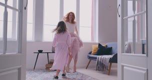 Actief jong mamma babysiter en leuk weinig jong geitjedochter springen die in moderne huiswoonkamer dansen, gelukkige familiemoed stock video