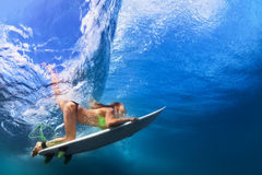 Actief meisje in bikini in duikvluchtactie betreffende brandingsraad stock afbeeldingen