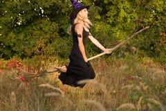 Actief meisje in de vliegen van het heksenkostuum op bezemsteel Stock Foto's