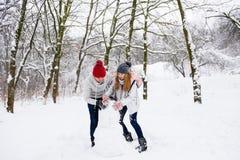 Actief paar van tieners die sneeuwman maken stock fotografie