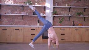 Actief vrolijk meisje die gymnastiek- tik doen en luchtkus in langzame motie verzenden bij keuken stock videobeelden