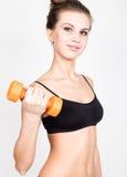 Actieve atletische vrouw met domoren die omhoog spierenbicepsen pompen Het concept van de geschiktheid Royalty-vrije Stock Foto