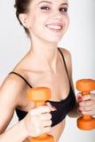 Actieve atletische vrouw met domoren die omhoog spierenbicepsen pompen Het concept van de geschiktheid Royalty-vrije Stock Foto's