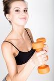 Actieve atletische vrouw met domoren die omhoog spierenbicepsen pompen Het concept van de geschiktheid Royalty-vrije Stock Afbeeldingen