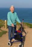 Actieve bejaarde damegepensioneerde in de jaren '80 met mobiliteitskader met drie wielen door kust Stock Afbeelding