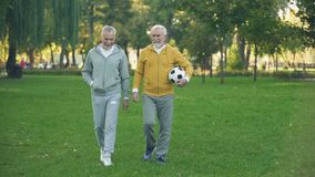 Actieve bejaarden die in park met voetbal, sporthobby, gezondheidszorg lopen stock videobeelden