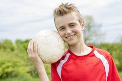 Actieve gelukkige jongen, die pret openlucht, speelvoetbal in de sportieve zomer hebben royalty-vrije stock foto's