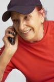 Actieve grandmama die op de mobiele telefoon spreekt stock afbeeldingen