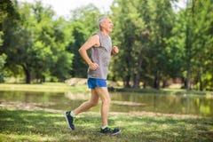 Actieve hogere jogging in een park en het luisteren aan muziek Royalty-vrije Stock Foto's