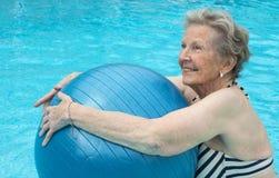 Actieve hogere vrouw in de pool, die oefeningen doen stock afbeeldingen