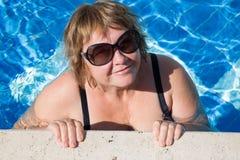 Actieve hogere vrouw die in blauw poolwater zwemmen Stock Foto's