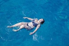Actieve hogere vrouw die in blauw zeewater zwemmen Royalty-vrije Stock Afbeeldingen