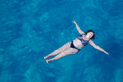 Actieve hogere vrouw die in blauw zeewater zwemmen Stock Fotografie