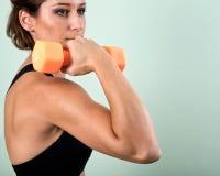 Actieve jonge vrouw die een oranje domoor voor haar wapenoefening gebruiken Stock Foto's