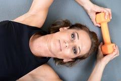 Actieve jonge vrouw die een oranje domoor voor haar wapenoefening gebruiken Royalty-vrije Stock Foto