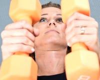Actieve jonge vrouw die een oranje domoor voor haar wapenoefening gebruiken Royalty-vrije Stock Fotografie
