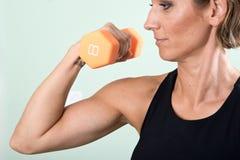Actieve jonge vrouw die een oranje domoor voor haar wapenoefening gebruiken Royalty-vrije Stock Foto's