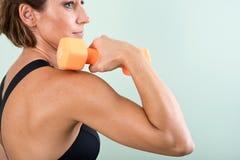 Actieve jonge vrouw die een oranje domoor voor haar wapenoefening gebruiken Stock Afbeeldingen