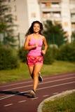 Actieve jonge vrouwenlooppas op atheltic spoor op de zomermiddag Royalty-vrije Stock Fotografie