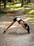 Actieve jonge vrouwentraining buiten, doend uitrekkende oefeningen op benen en handen op de linkerkant, op parkachtergrond stock foto