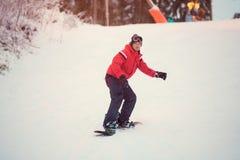 Actieve mens snowboarder in rood jasje die op helling, het snowboarding berijden Royalty-vrije Stock Foto