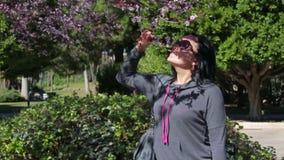 Actieve mooie vrouw die een bloem van een boom ruiken stock videobeelden
