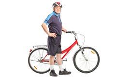 Actieve oudste die een fiets en het stellen duwen Stock Foto