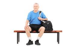 Actieve oudste die een sportenzak gezet op bank dragen Stock Foto