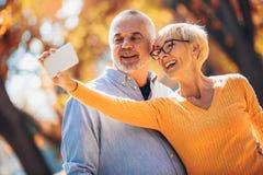 Actieve oudsten die selfies van hen nemen die pret hebben royalty-vrije stock afbeeldingen