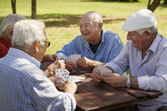 Actieve oudsten, groep oude vriendenspeelkaarten bij park Stock Foto's