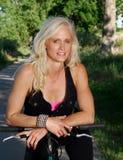 Actieve rijpe vrouw op een fiets stock afbeelding
