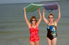 Actieve rijpe vrouwen bij strand Stock Foto's
