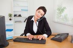 Actieve secretaresse die de telefoon beantwoordt Royalty-vrije Stock Foto
