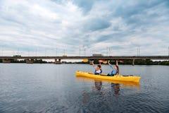 Actieve sportmannen die in kano roeien die hun peddels opheffen stock fotografie