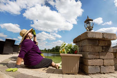 Actieve teruggetrokken dame die een onderbreking van het tuinieren nemen Stock Afbeelding