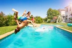 Actieve tienerjaren die zomer doorbrengen door de pool stock foto's
