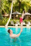 Actieve vader die zijn peuterdochter onderwijzen om in pool bij de tropische toevlucht te zwemmen Stock Foto