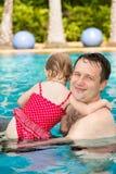 Actieve vader die zijn peuterdochter onderwijzen om in pool bij de tropische toevlucht te zwemmen Royalty-vrije Stock Foto's