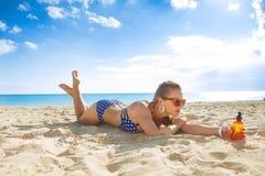 Actieve vrouw in strandkleding op zeekust met zonblok het leggen royalty-vrije stock afbeelding