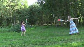 Actieve zwangere vrouw met het badmintonspel van het meisjesspel in park Stock Foto