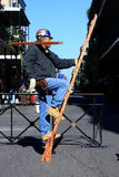 Constructor. An actor performing a street show in which he pretends to be a constructor walking up a ladder to continue with his building work Royalty Free Stock Images