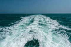 Acting wave behind motor boat. At the vast ocean Royalty Free Stock Image