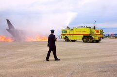 Action. A fire chief coordinating with a walkie-talkie the actions of a yellow fire truck attending to a burning mock-up plane during an open house fire drill Royalty Free Stock Photos