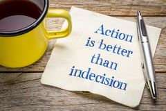 Action is better than indecision. Handwriting on a napkin with a cup of tea Royalty Free Stock Photos